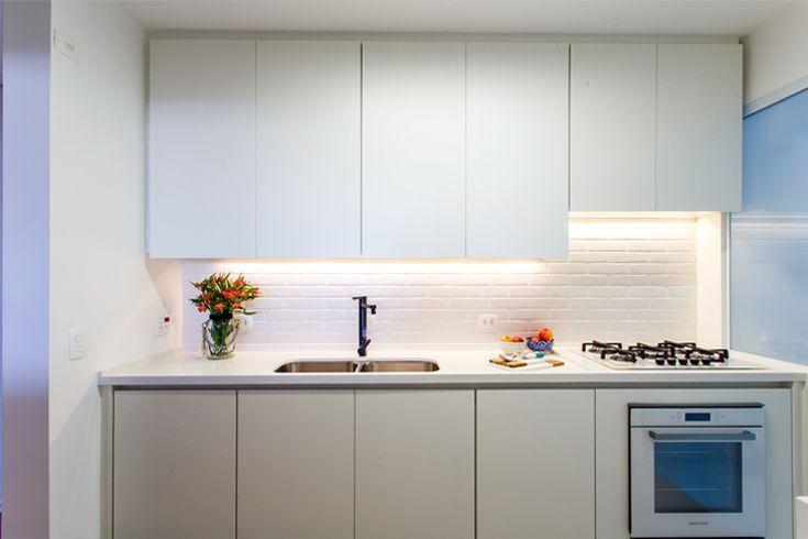 Cozinha branca e clean. Tijolinhos brancos, bancada branca, torneira preta, cooktop e forno brancos.