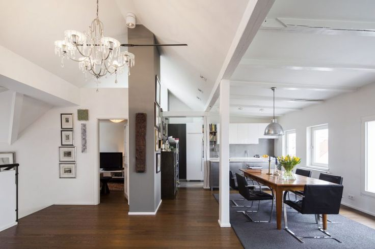 Grey and white modern dining room furnished with a big wooden table, Ludwig Mies van der Rohe Brno chairs,grey carpet, big chandelier and a collection of pictures on the wall.#kitchen #diningroom #grey #white #open #neutral #luxury #interiordesign #design