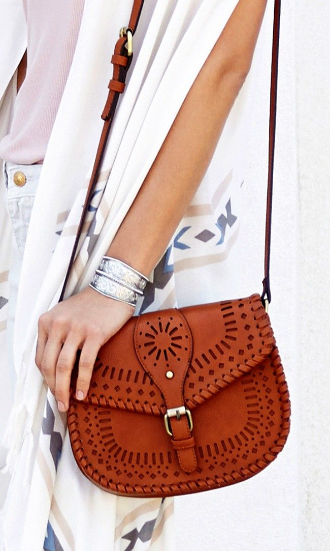 Boho vibes: Vintage-inspired cognac crossbody saddle bag with intricate laser cut detailing and fold-over snap closure