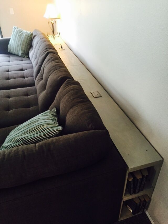 Behind The Couch Shelf With Electrical Outlets And Side Book