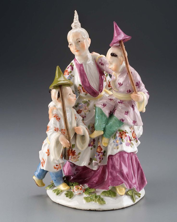 """Modelled by P. Reinicke after Boucher's """"Lee Delices de L'Enfance"""". Chinese family: Mother seated, in robe decorated with Indianische blumen over puce undergarment; at her right a child in robe with iron-red floral pattern and blue trousers, at her left on her knee another child with parasol, rose robe with turquois; shaped base with polychrome flowers; mark: underglazed blue crossed swords underneathbase."""