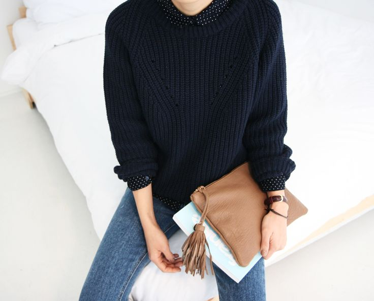Navy blue sweater and blue jeans with a tan clutch