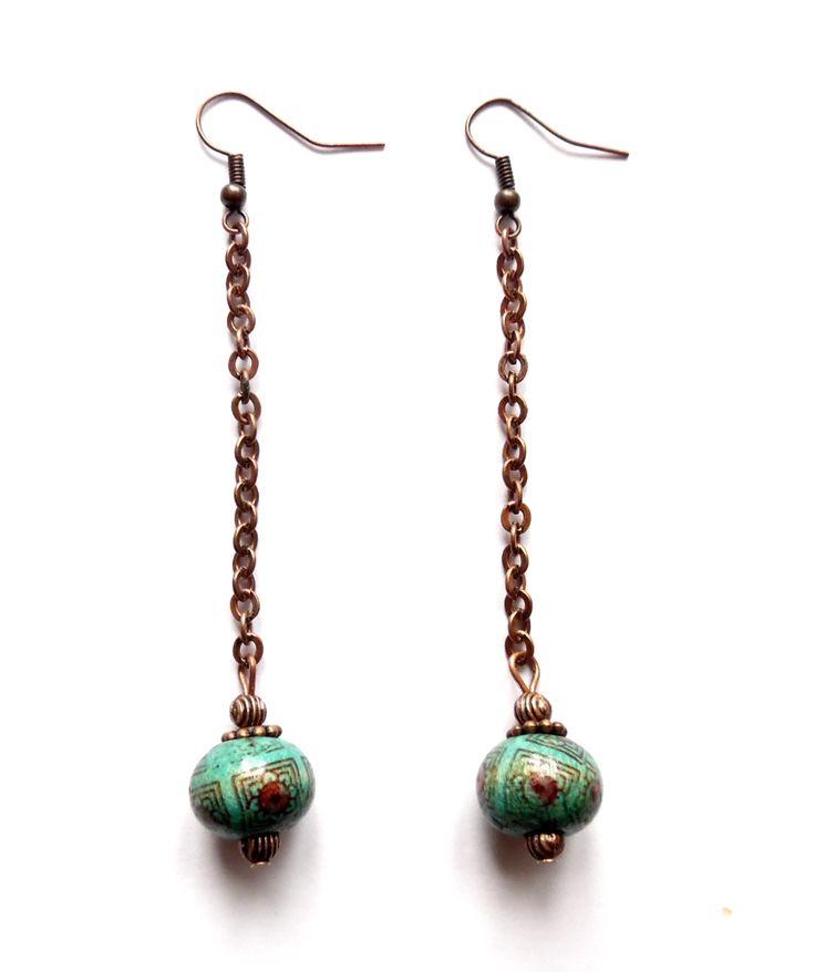 Örhängen i koppar med turkos mönstrade pärlor av trä.  Längd: 9cm