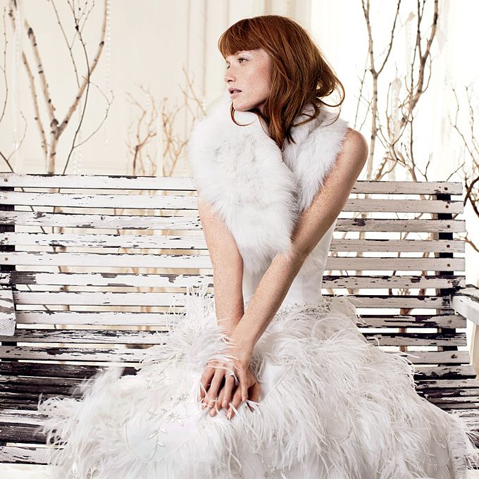 Brides.com: Modern Winter Wedding Dresses. Ivory French-tulle strapless ball gown with a feather-and-sequin skirt, $1,900, Karelina Sposa; Fox stole, $1,275, Adrienne Landau; Diamond ring set in 18-karat white gold, Simon G.   Browse more Karelina Sposa wedding dresses.