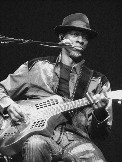 """Keb' Mo' (born Kevin Moore, October 3, 1951) is a a three-time Grammy Award winning blues musician. He is a singer, guitarist, and songwriter, currently living in Nashville, Tennessee. He has been described as """"a living link to the seminal Delta blues that travelled up the Mississippi River and across the expanse of America."""" His post-modern blues style is influenced by many eras and genres, including folk, rock, jazz and pop. The moniker """"Keb Mo"""" was coined by his original drummer."""
