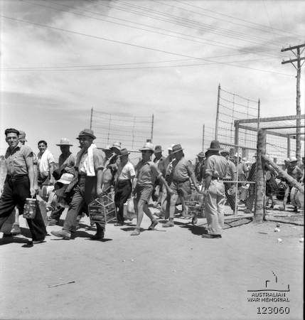 Barmera, South Australia. 1943-12-31. As many Italian internees were released during 1943 it was decided to close No 9 Compound and transfer the remaining Italians to No 14D Compound in the Loveday Internment Camp Group. This photograph shows internees passing through the compound gates carrying their personal belongings including birds in cages.