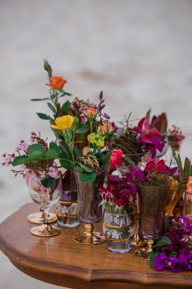 A variety of wine glasses and goblets each holding a flower grouped together for impact.