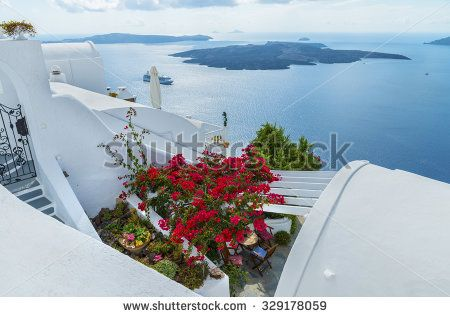 Beautiful bougainvillea blooming in the courtyard of a traditional Greek home and wonderful views of the volcano and the Caldera.Santorin island.Cyclades.Greece.Europe.