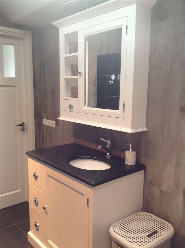 Landelijke badkamer. Houtlooktegels gecombineerd met donkere tegels en een mooi wit badkamermeubel.