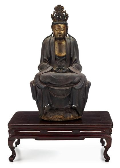 Chinese gilt wood seated bodhisattva     Ming dynasty     The diety seated on a rocky ledge in dhyanasana with hands folded in his lap and eyes downcast, robes open at chest; with associated hongmu low table as stand.     H: 31 in.