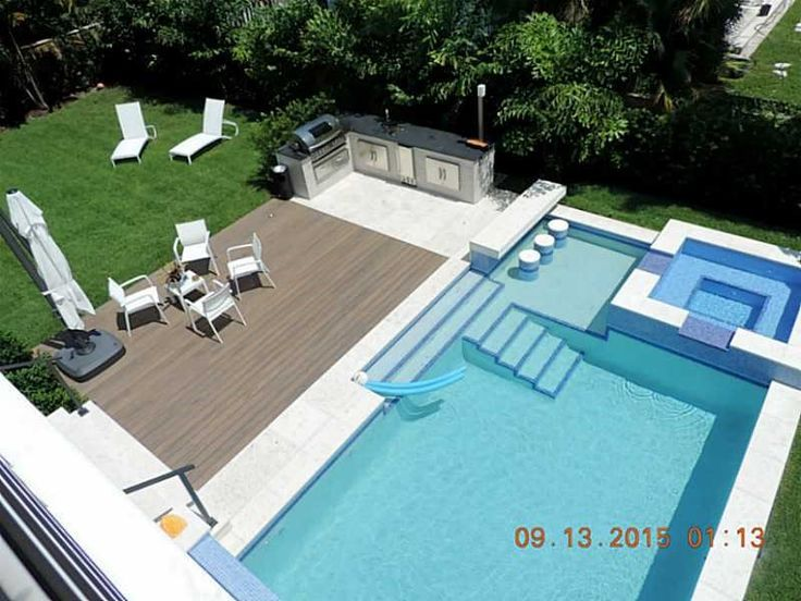 Swimming pool with swimup bar connected to outdoor kitchen