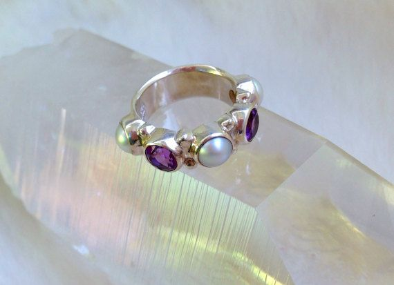 This exquisite Sterling Silver Ring features two stunning facetted Amethysts and three White Pearls. PEARL - the ancient gemstone of the sea. The pearl is the oldest known gem, and for many centuries it was considered the most valuable. Unlike all gems, the pearl is organic matter derived from a living creature - oysters and mollusks. Pearls symbolize Purity, Spiritual Transformation, Charity, Honesty, Wisdom and Integrity, all the best within us. Pearls provide a clear vehicle for the…