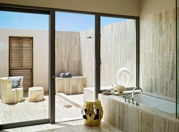 Ванная комната в отеле Viceroy Anguilla с выходом на небольшую закрытую территорию под открытым небом. Благодаря единой мраморной стене уличный душ составляет общее пространство с крытой ванной. Раздвижные стеклянные двери могут разделить зоны или, напротив, объединить помещение для отдыха и релаксации на свежем воздухе.Фото: Viceroy Anguilla.