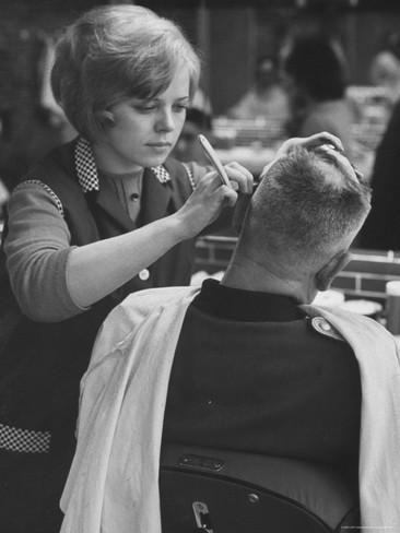 Female Barber Cutting a Customer's Hair in a Barber Shop Lámina fotográfica