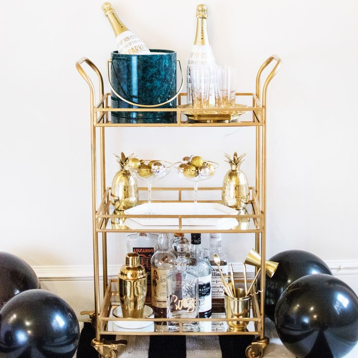 """This three layered glass shelf is in a brushed gold frame. It's wheels make it easy to move around as the party does! Dimensions: 23""""L x 13""""W x 34""""H Materials: Gold Finished Metal with Glass"""