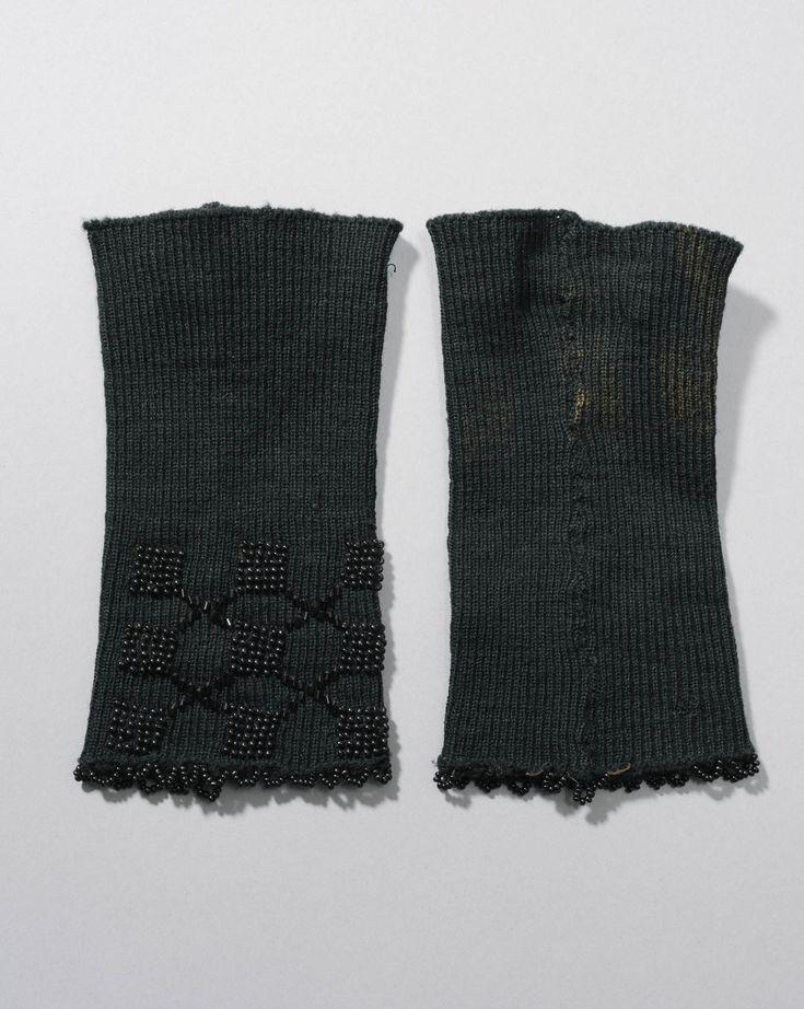 Machinaal gebreide polsmoffen van fijne zwarte wol, versierd met ingebreide kraaltjes in geometrisch patroon. Axel #Axel