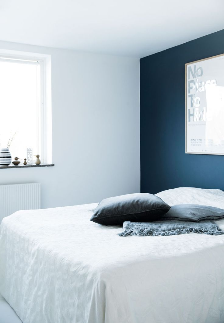 Spotless white and shades of gray, deep petrol blue accent wall