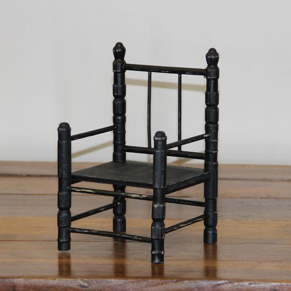 Black finish with light distressing give a vintage feel to this wooden doll chair, with turned legs.