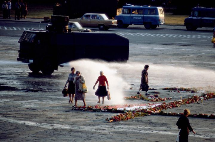 Chris Niedenthal | Milicyjna armatka wodna przepędza kobiety przy krzyżu z kwiatów na placu | Warszawa, 16 sierpnia 1982, Plac Zwycięstwa (dzisiaj Plac Piłsudskiego)