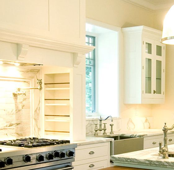 Bakes and Company  Gorgeous kitchen design with wood paneled kitchen hood, white glass-front kitchen cabinets, marble countertops, pot filler, marble subway tiles backsplash, stainless steel apron sink, sink in kitchen island and drop-down island with wood countertop.
