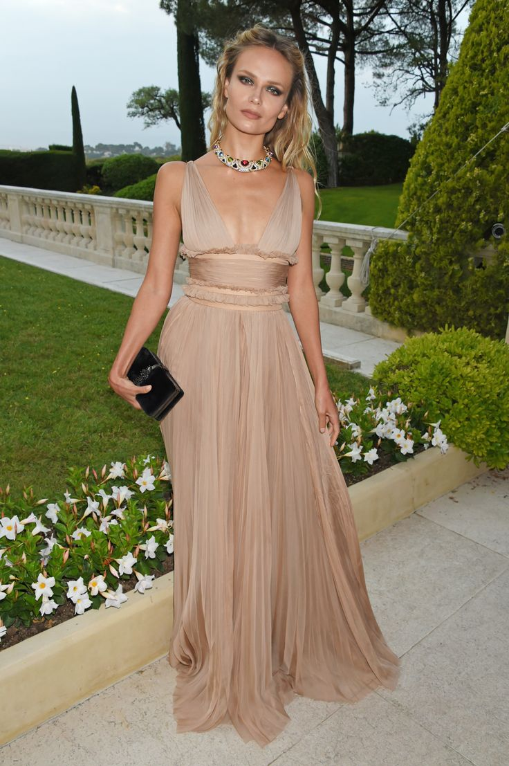 Model Natasha Poly wore a vintage Bulgari cuff necklace from 1988 in gold with amethysts, red tourmalines, peridots, citrines and diamonds. She looked Grecian in her flowing chiffon champagne coloured dress with plunging neckline and beach waved hair. At the amFAR Gala. For glamour celebrity fashion Cannes Film Festival red carpet jewellery spotting travel here: http://www.thejewelleryeditor.com/jewellery/top-5/cannes-film-festival-amfar-gala-2017-red-carpet-jewellery/ #jewelry
