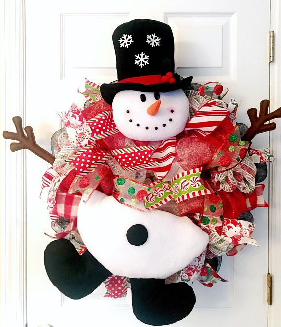 Frosty the snowman ⛄️ has jumped into this wreath! This wreath is such a conversation piece and will definitely make your guests smile! It's impossible not to. This wreath was constructed using white metallic, red metallic, red and green stripe and black high quality decomesh. The stuffed