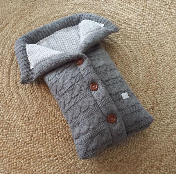 En herlig grå kabelstrikket vognpose perfekt til bagdelen. Lun og god til babyen vår og høst. Lukkes med brune treknapper og har lysegrå myk fleece inni.