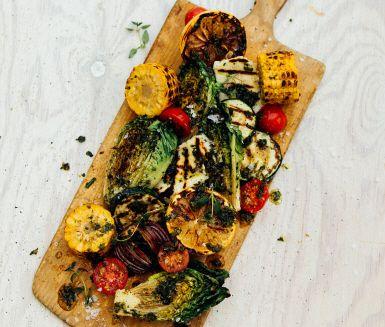 Här får grillad hjärtsallad sällskap av halloumi och goda färgsprakande grönsaker. Grilla, lägg på fat och ringla över vitlök- och timjanolja. Välkommen till smakhimmelen.