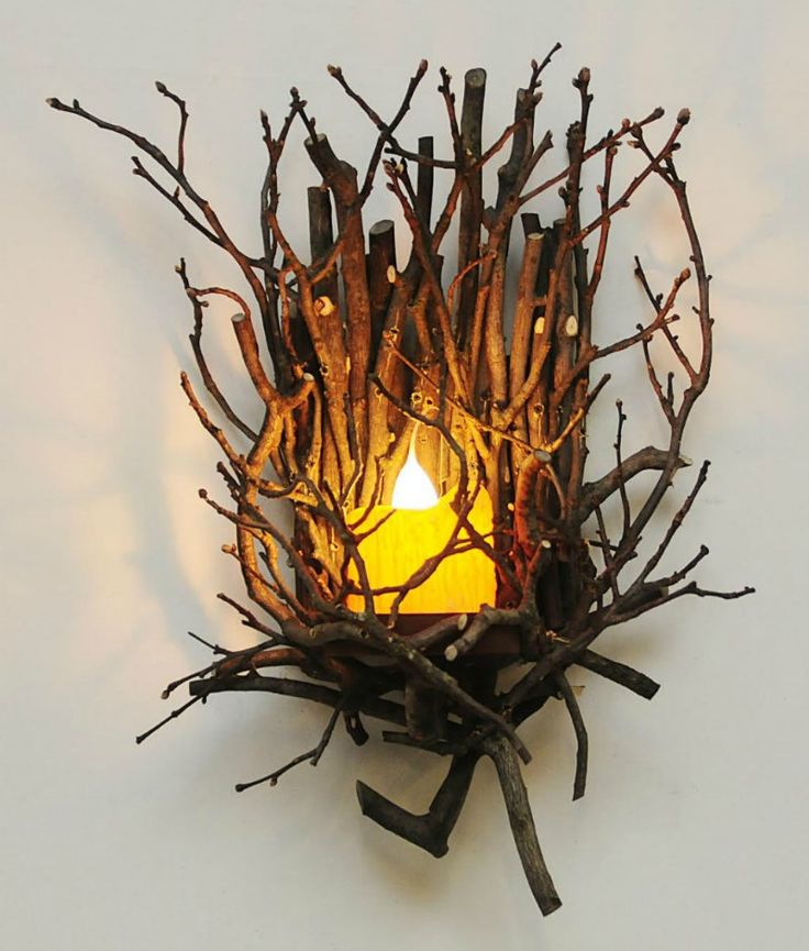 For rustic elegant decor this wall sconce is handcrafted from hickory twigs. Wired with a white pillar candle with hand dipped bulb. Hardwire or plug in.