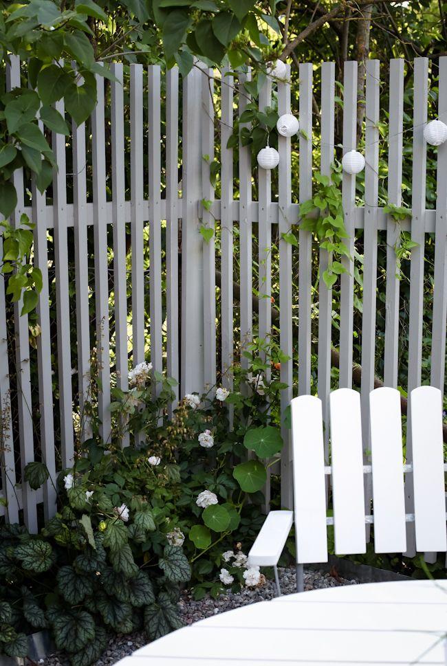 Enkel klassisk avskärmning med spaljé (högt staket) med smala stående vita ribbor.
