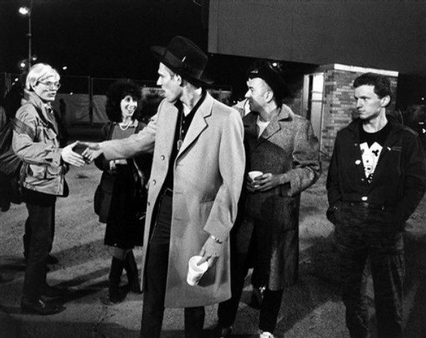 In this 1982 image released by Epic/Legacy Records, artist Andy Warhol, left, and publicist Susan Blond, second left, are shown backstage with members of The Clash, Paul Simonon, center, Joe Strummer and Terry Chimes, right, at Shea Stadium in New York.