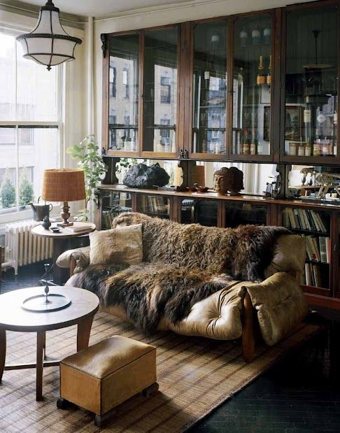 Roman and Williams; that buffalo hide is outrageous! Love the shelving and display behind the couch <3