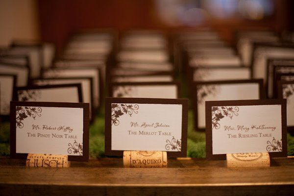 cut the corks so they have flat bottoms and slits. at 40 guests, not horrible to do yourself. also make these for holding up other signs?