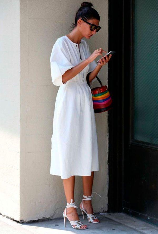 Vestido branco com sandália branca e bolsa colorida.