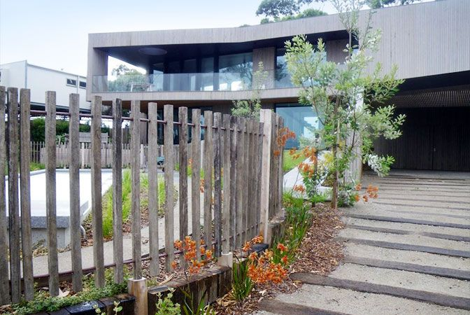 Simple picket fence and complimentary path of wooden 'sleepers' laid in sand