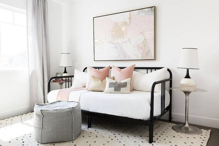 Pink and black guest room features a pink and gold abstract art piece placed over a black daybed dressed in blush pink pillows as well as a gold metallic pillow flanked by round silver nightstands topped with black and white rugs.