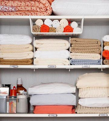 The perfect linen closet: hanging bin for wash cloths, slide on shelf dividers to keep towels in place and rods on the doors to hang table cloths from . . . all perfectly labeled.  Love it!
