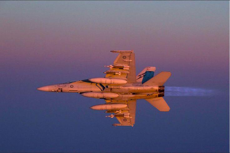 A Royal Australian Air Force F/A-18F Super Hornet ignites its afterburners at dusk over Iraq