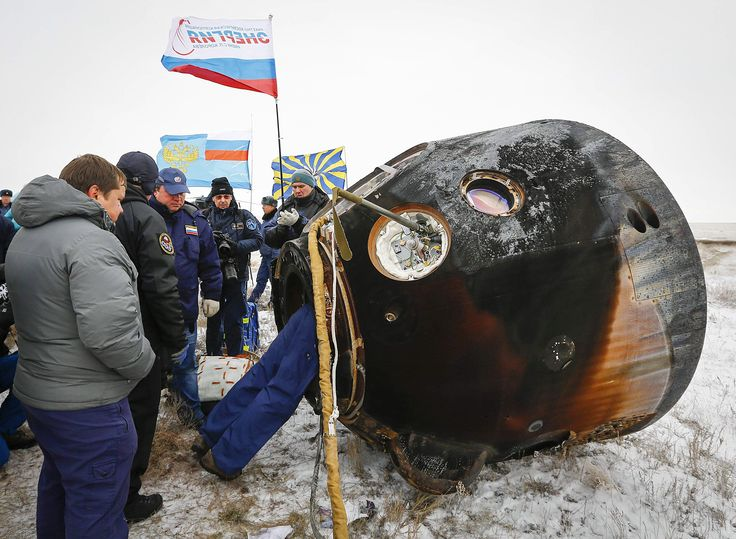 Ground personnel work on the Soyuz TMA-13M capsule, carrying International Space Station crew members Alexander Gerst of Germany, Maxim Surayev of Russia and Reid Wiseman of the US, after its landing near the town of Arkalyk in northern Kazakhstan. ■ Photo: Shamil Zhumatov (AFP)