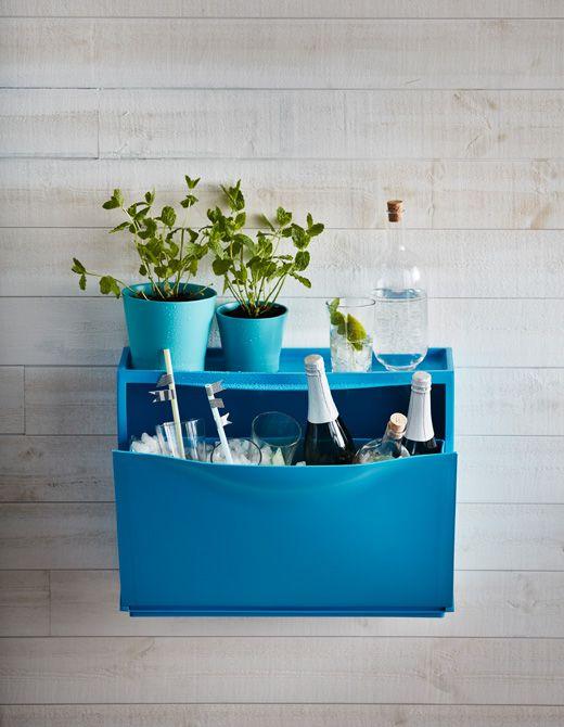 Eine blaue IKEA TRONES Aufbewahrung gefüllt mit Eis, Gläsern und Sektflaschen. Obendrauf Pflanzen und zwei Gläser.