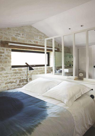 Une verrière blanche qui sépare la chambre de la salle de bains