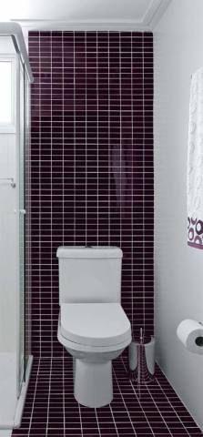 """Banheiro 1 – 2,93 m²: Na área do vaso, criaram uma faixa contínua do piso à parede com pastilhas de vidro berinjela (linha Studio, recesa). """"Ela parece prolongar o espaço"""", fala a arquiteta."""