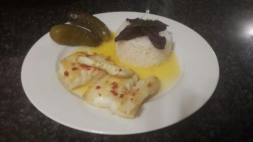 Grilled kingklip with orange chilli butter sauce, server with rice and gherkin.