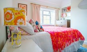 A bright pink and yellow bedspread and orange and yellow floral lampshade stands out in a plain and pale painted bedroom.