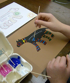 """4th grade began by drawing & cutting out a black paper silhouette of an animal. """"Then students drew one or two x-ray drawings: an image of one of the animal's bones or organs. The last step was to add patterns of dots to their animals using tempera paint and swabs. Students included an Aboriginal symbol, concentric circles, on the backgrounds of their artworks.  The concentric circle stands for family, or a village."""""""
