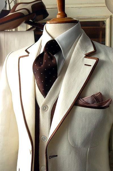 Men's ivory blazer piped in brown, contrasting knit vest, ivory shirt brown tie w/ ivory polka dots.