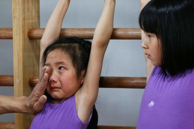 Un entrenador limpia las lágrimas a una niña durante una clase de gimnasia en la Escuela de Atletismo Yangpu en Shanghai, China. Estos niños no disfrutan su infancia.