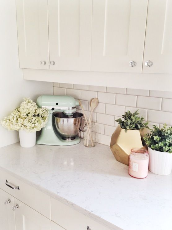 creamy white shaker style kitchen cabinets, subway tile back splash, crystal knobs, nickel pulls, quartz counters