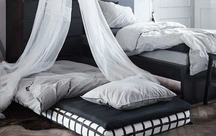 Dva menšie matrace uložené na zemi vedľa postele a upravené ako posteľ navyše s baldachýnom nad ňou.