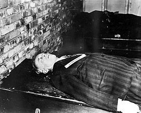 A corpse dressed in a black suit lies facing up on a table next to a brick wall. Only the upper torso is visible.-Ulrich Friedrich Wilhelm Joachim von Ribbentrop (30 April 1893 – 16 October 1946) was Foreign Minister of Nazi Germany from 1938 until 1945. A successful businessman, he was appointed German Ambassador to London in 1936.